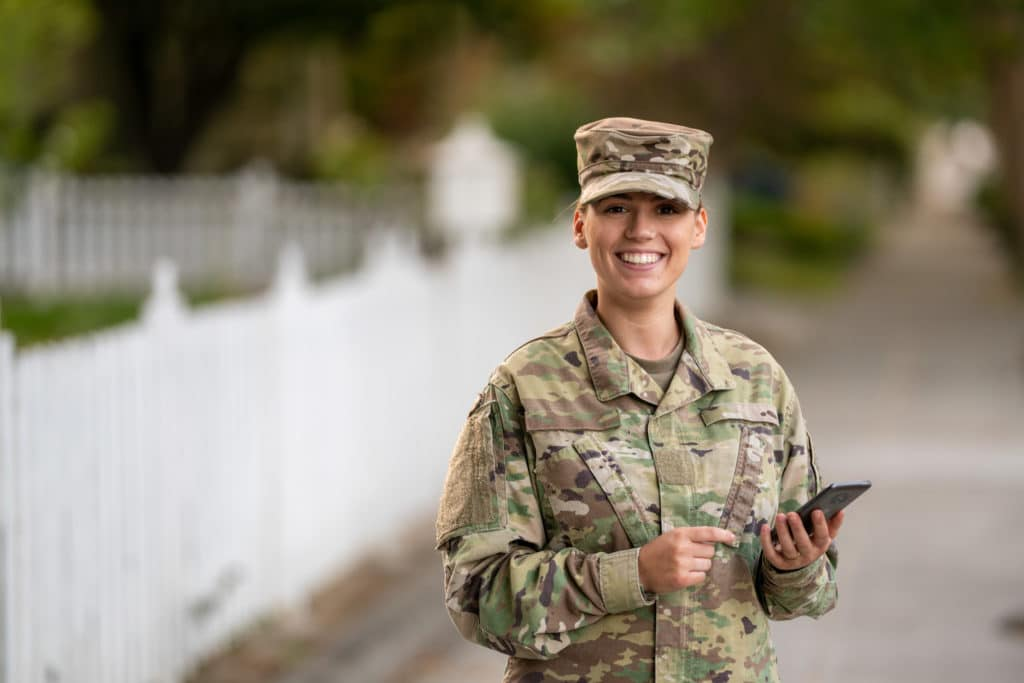 US Military off duty woman using cell phone outside.