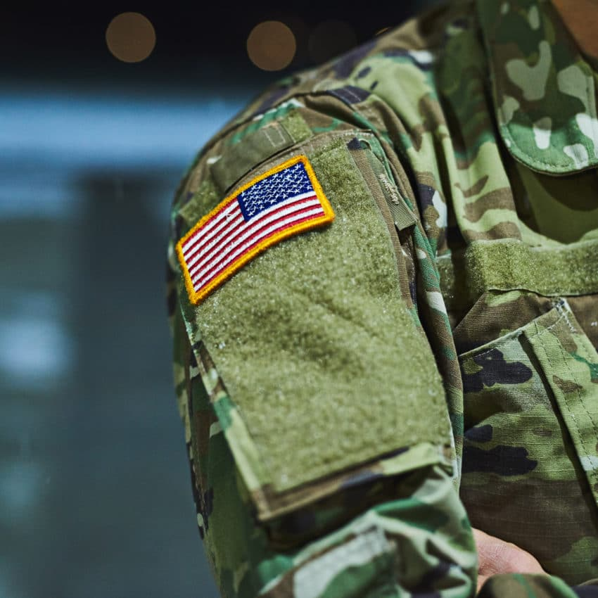 Cropped shot of a soldier wearing camouflage fatigues with an american flag for a patch